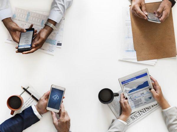 4 osoby na spotkaniu biznesowym sprawdzają telefony