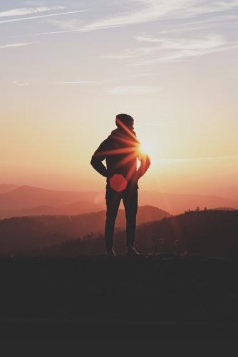 Człowiek stoi tyłem do aparatu w górach ogląda zachód słońca