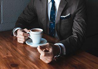 dłonie biznesmena, które trzymają filiżankę kawy