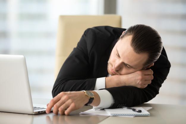 Biznesmen śpi na biurku