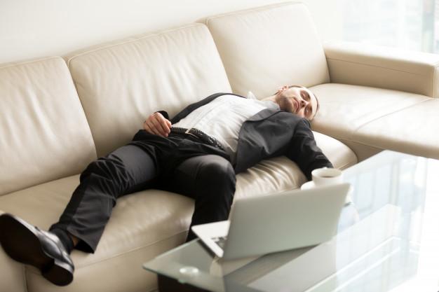 biznesmen śpi na sofie