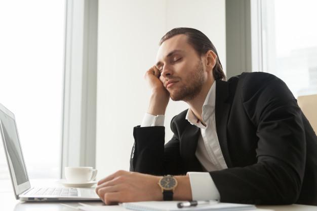 młody biznesmen śpi przy laptopie